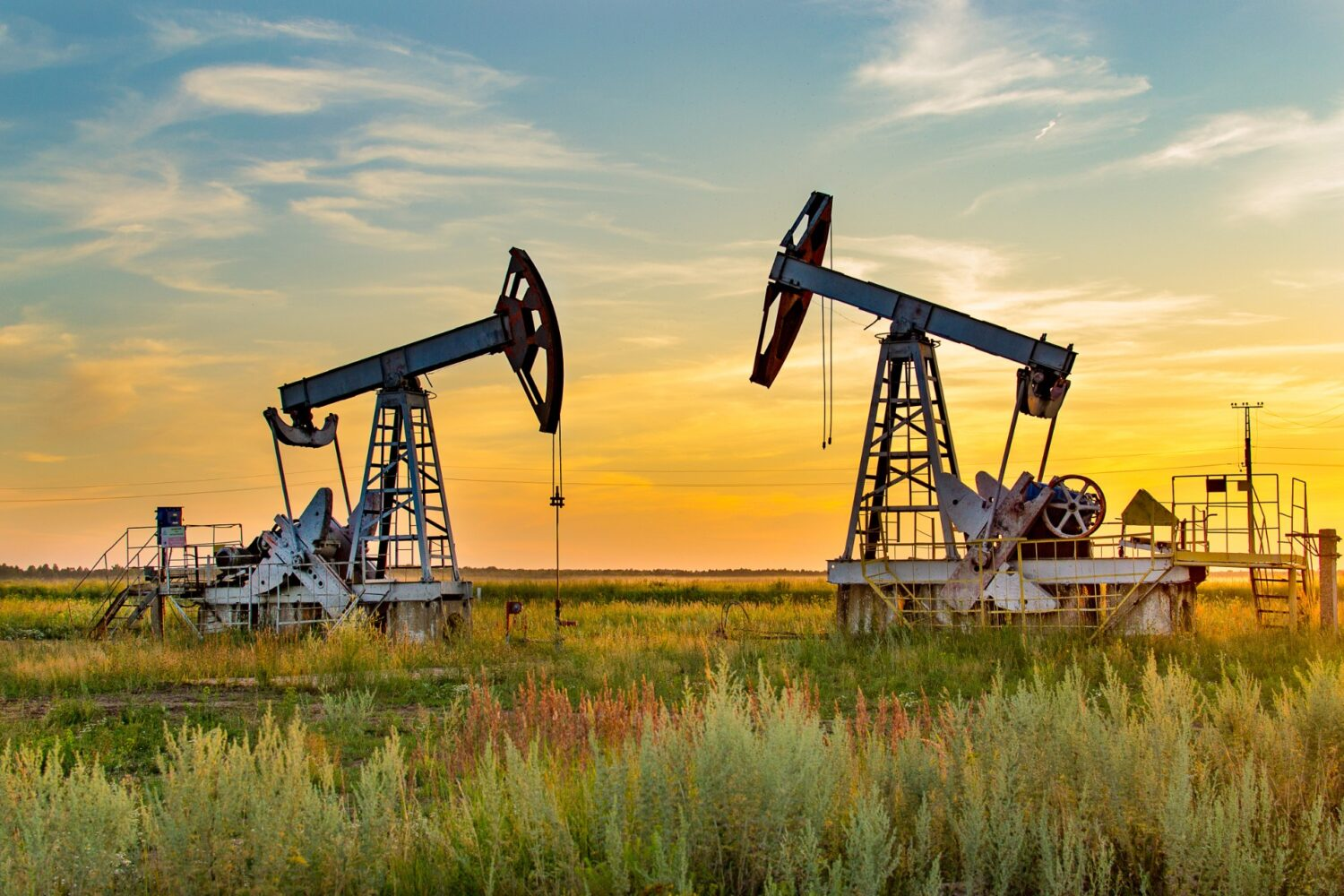 Two oil wells green grass blue sky yellow horizon